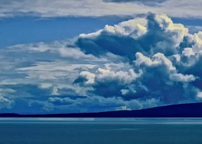 billowing clouds over small island